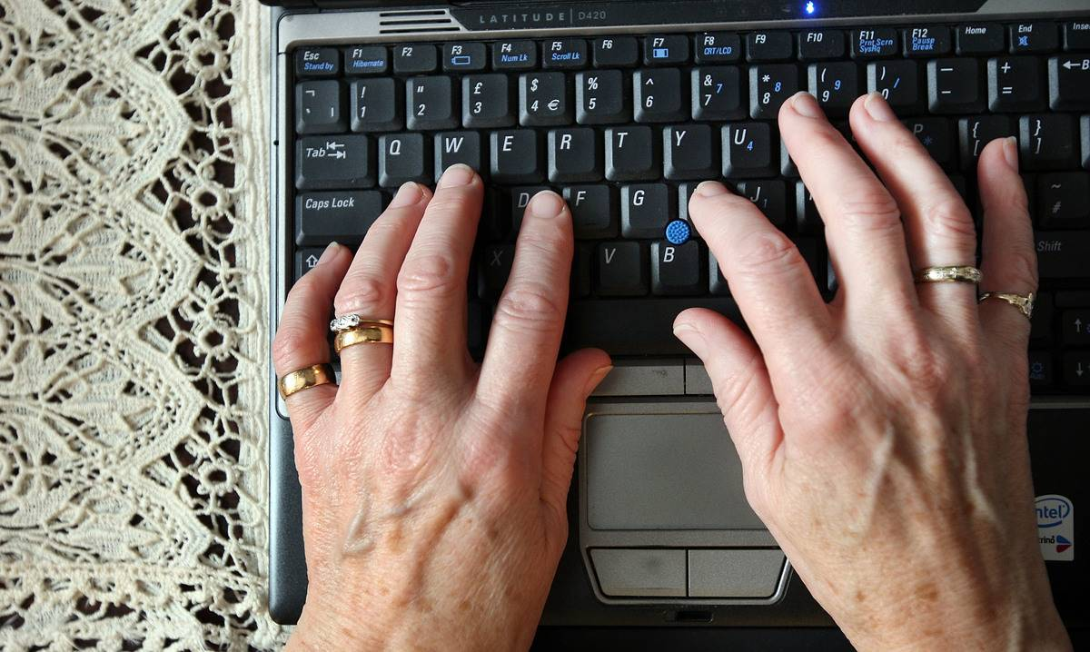 An elderly woman types on a laptop.