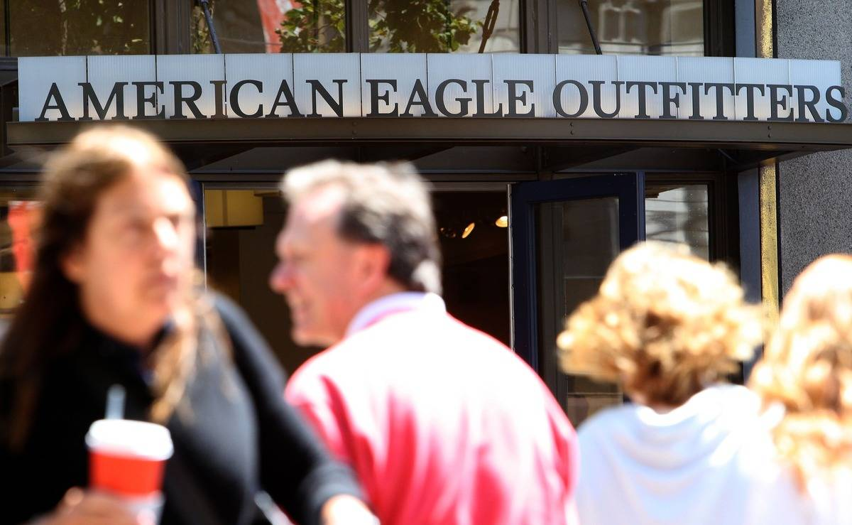 People walk in front of an American Eagle Outfitters store.