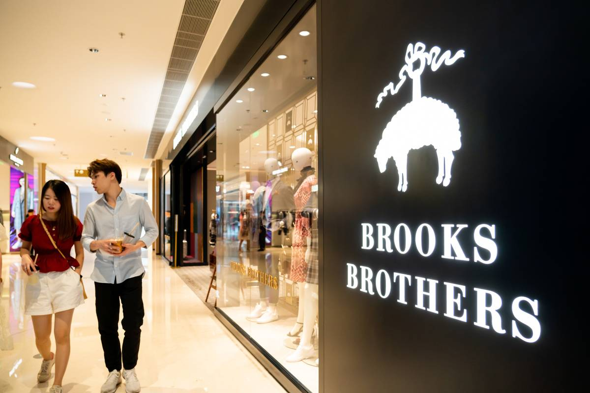 A couple walks past a Brooks Brothers store in a mall.