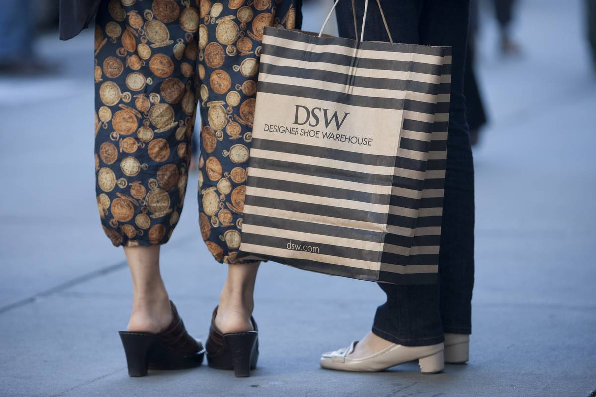 Shoppers carry a bag from DSW Inc. shoe store.