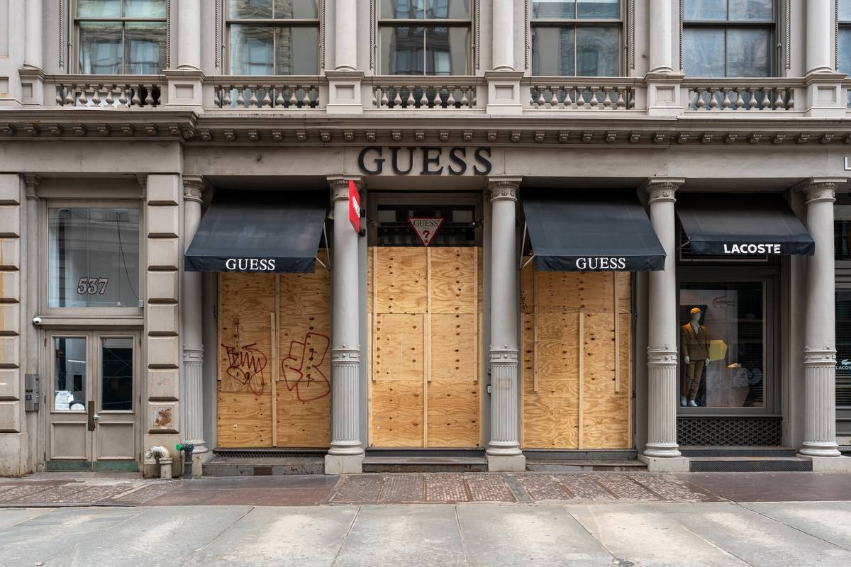 A Guess storefront is boarded up.