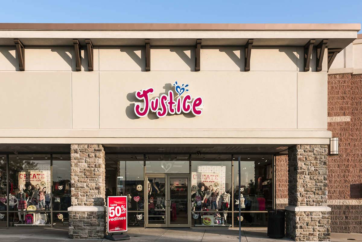 A Justice clothing store is closing with a 50% off sale sign out front.