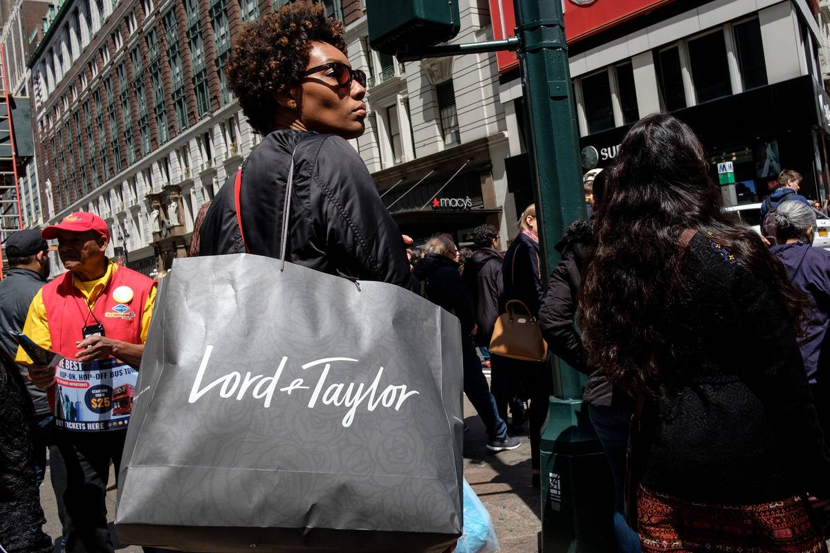 A woman carries a Lord & Taylor shopping bag.
