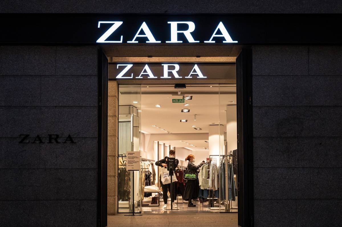 Shoppers are seen inside of a Zara store at night.