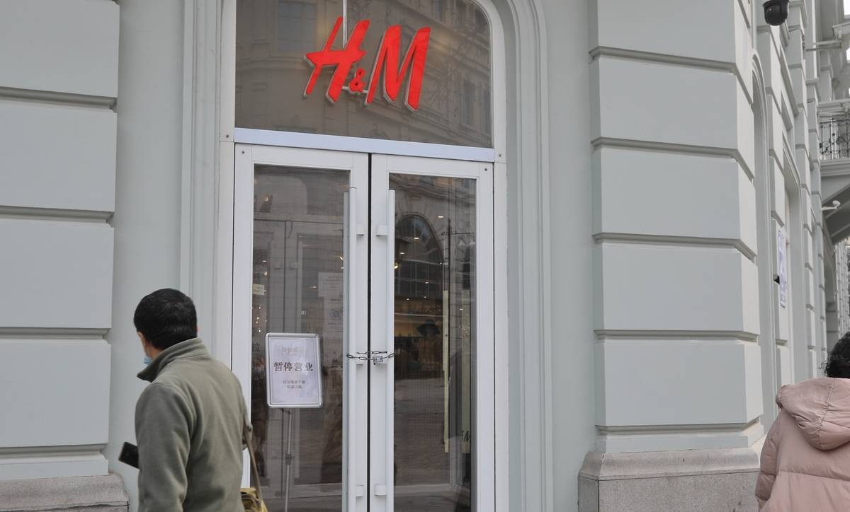 A man walks in front of a closed H&M store.