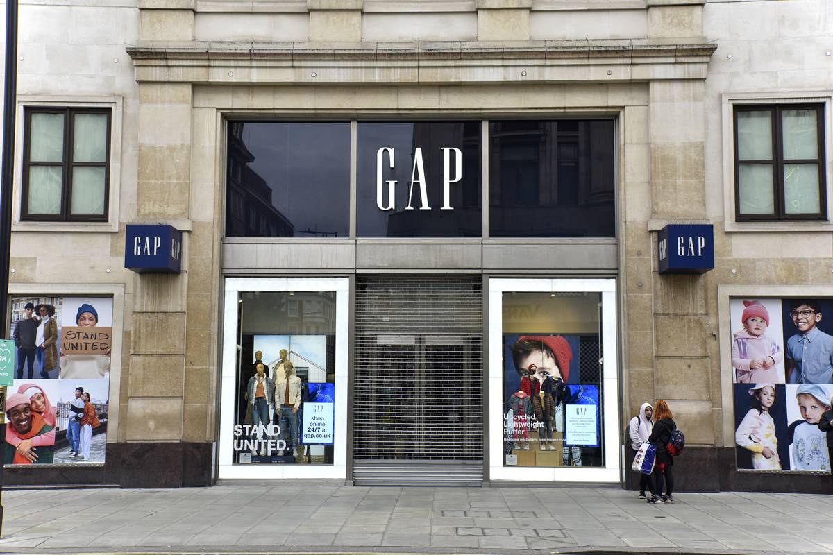 People walk outside of a Gap store that is closed down.