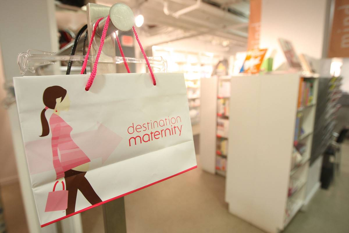 A Destination Maternity shopping bag hangs in a store.