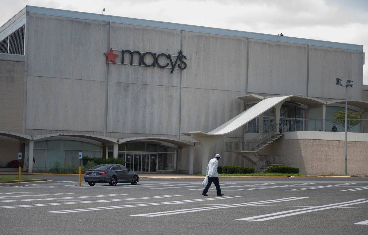 One person carries a bag across an empty Macy's parking lot.