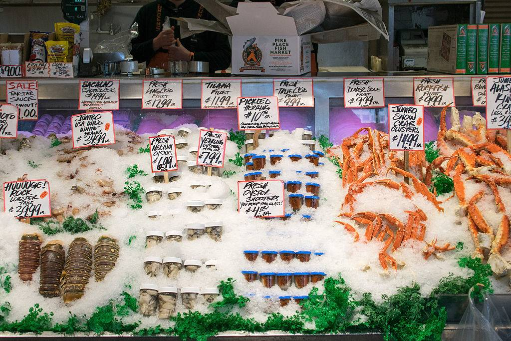 Lobsters, crab legs, oyster shooters, and a variety of seafood for sale at a shop