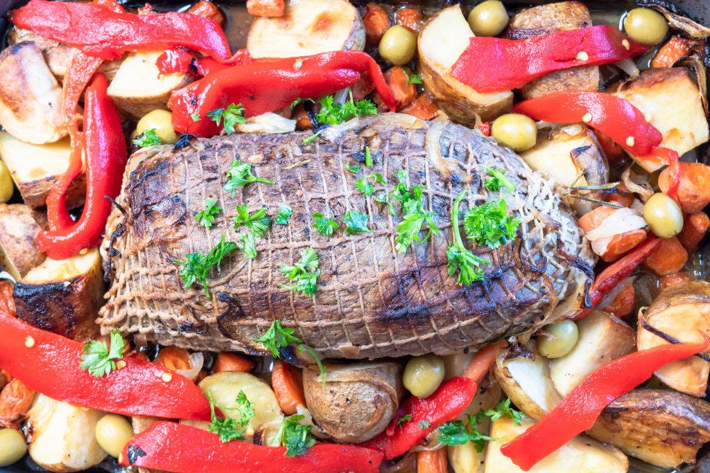 A roasted beef sirloin tip on a tray and surrounded by baked potatoes and peppers