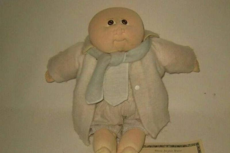 A 1979 Little People doll Andrew Blair is pictured with his adoption papers.