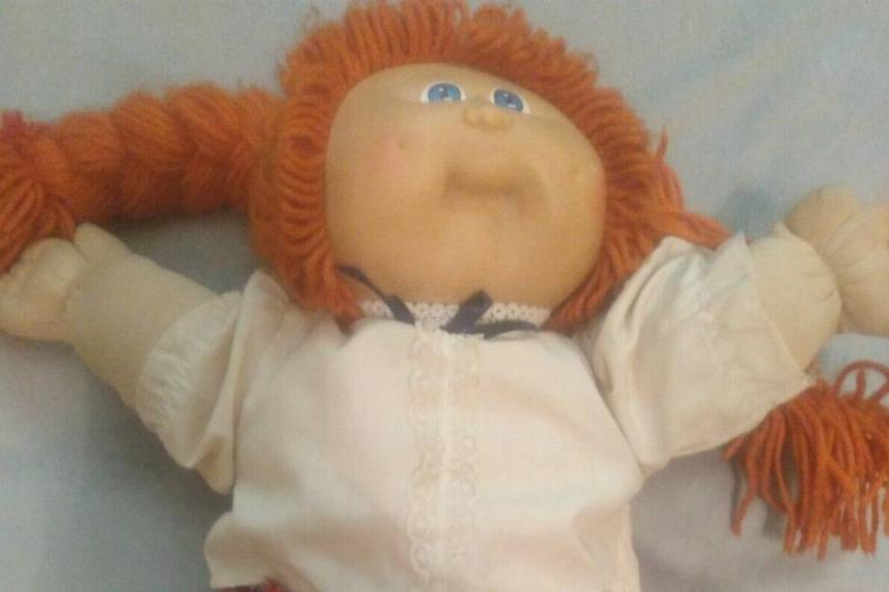 An Ann Greta Cabbage Patch Kids doll is laid out on a bed.