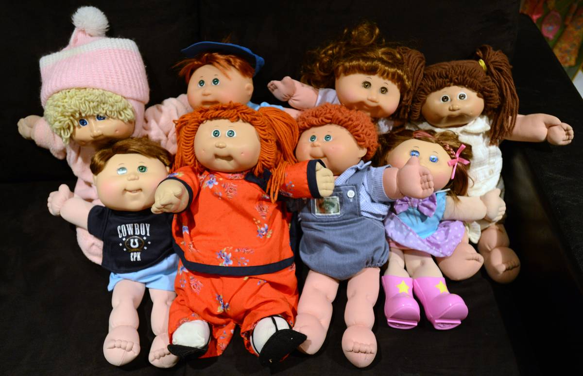 Several Cabbage Patch Kids sit in a pile.