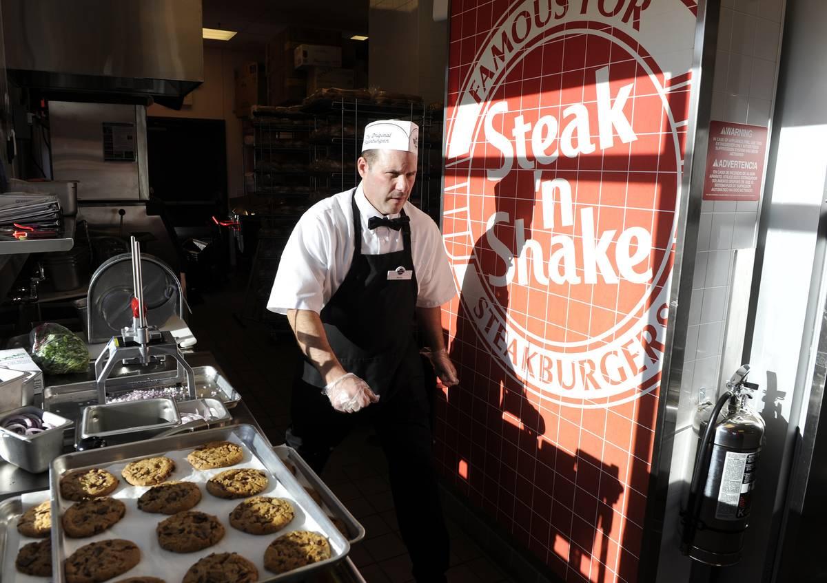 Steak'n Shake employee, Steve Jones, walks to his next task in the kitchen before the grand opening of the Steak'n Shake in Centennial Thursday morning. Andy Cross, The Denver Post