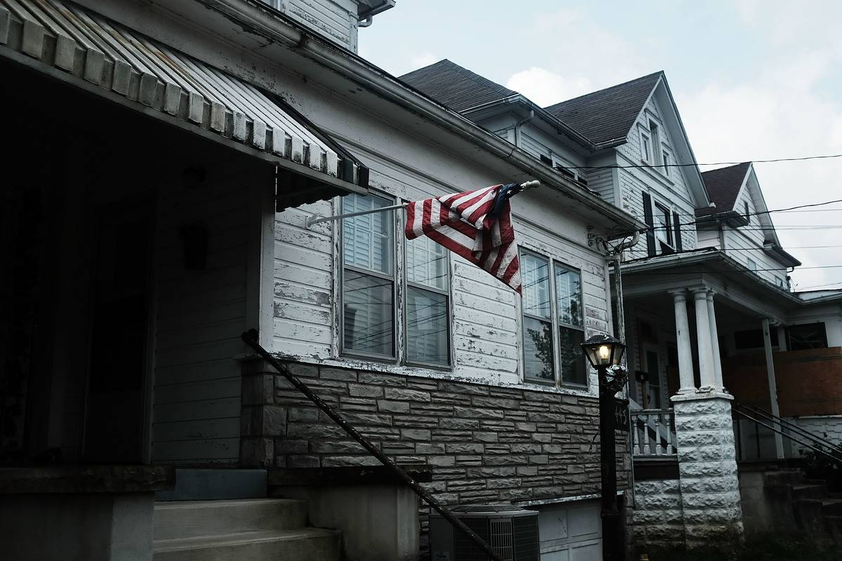 An American flag is tangled above two impoverished homes in West Virginia.