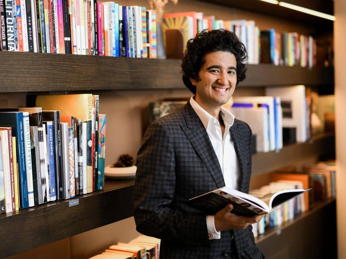 Benjamin Arabov smiles while a reads a book.
