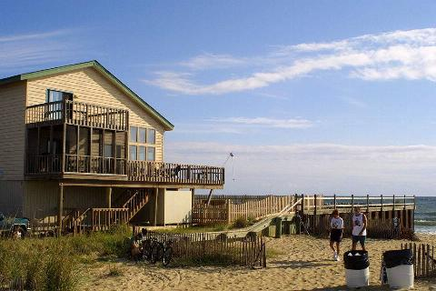 a house on the beach with people walking in the sand in Virginia Beach, Virginia