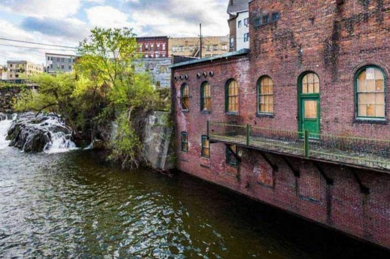 an old building near a river in brattleboro, vermont