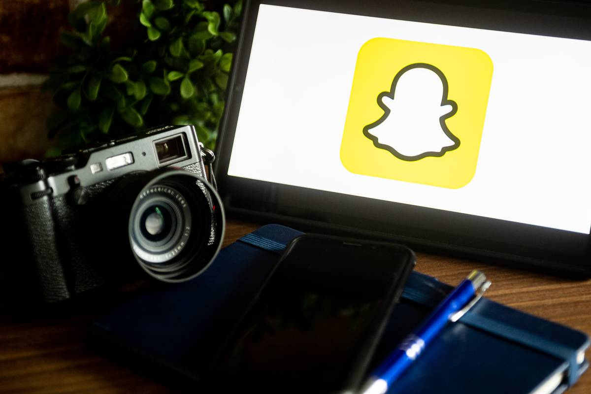 The snapchat logo is seen on a screen next to a camera and phone.